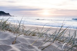 sunrise light on white sand beach with dune grass in Australia with surf waves of the pacific ocean