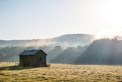 Sunrise morning silhouette of agricultural abandoned brick storage barn shed in autumn landscape farm field in rural countryside of West Virginia with fog mist sun sunrays by rolling hills