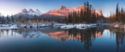 Sunrise of the Three Sisters and the Bow River from Canmore near Banff National Park. First snow in Canadian Rockies. Beautiful landscape background concept. Christmas time