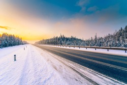 Sunrise on a clear winter morning, an empty country road to snowfall passing through a coniferous forest. View from the side of the road. Russia, Europe. Beautiful nature. Orange-blue toning effect.