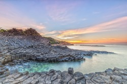 Sunrise on Giant's Causeway with volcanic rocks like hexagonal pillars put them in the sea, far away is the sun rises with the light signal a new day on the sea Beautiful Vietnam