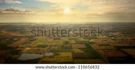 Sunrise on Horizon - illustrated sunrise over an aerial view of South Dakota farm land