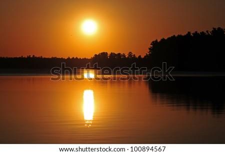 Sunrise on lake with pine trees along the horizon
