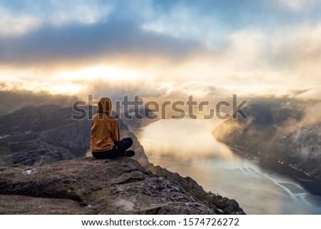 Sunrise on pulpit rock. Girl looking on fjord Zdjęcia stock ©