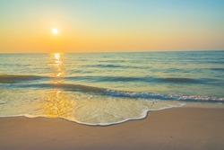 Sunrise on the beach - vintage filter. Sea waves lash line impact rock on the bea. Seaside under a rough sky.