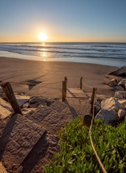 sunrise on the beach with stairs and rocks