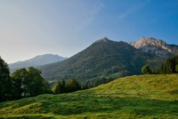 Sunrise on the bench in the Alps in the background on a sunny day with blue sky and clouds in summer, National park Berchtesgadener Land, Upper Bavaria, Germany