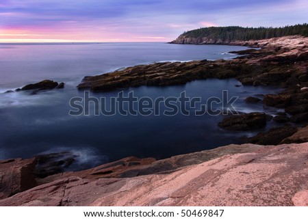 Sunrise on the coast of Maine at Acadia National Park.  The sun is rising over Otter Cliffs with a long exposure of the water.  Pink granite sits in the foreground as an accent.