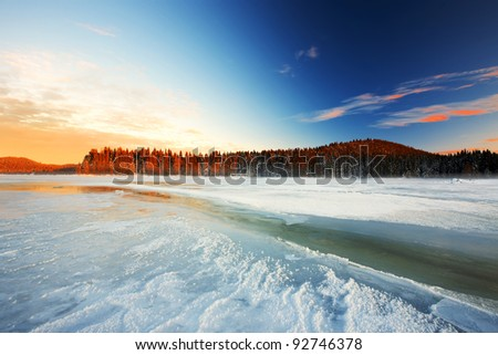 sunrise on the frost lake in wild area