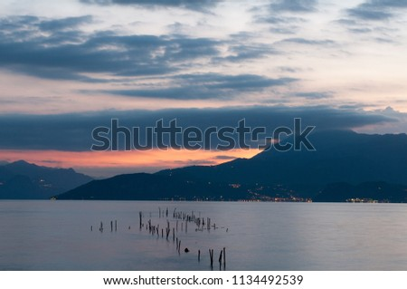 Sunrise on the lake. Early morning landscape. mountain in silhouettes and the rays of the rising sun.Sunrise on Lake Garda, Italy. #1134492539