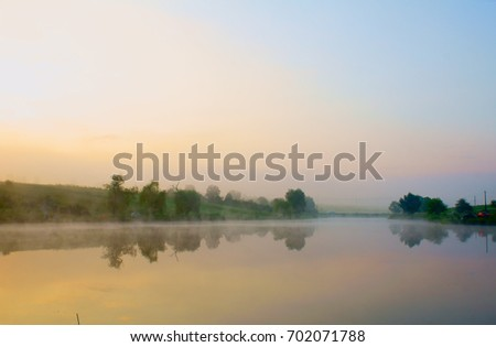Sunrise on the lake with blue water. mist