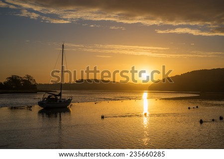 Sunrise on the river lynher with beautiful sky and golden reflections at st germans, cornwall, uk