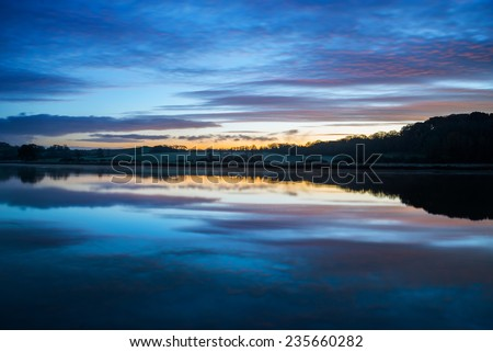 Sunrise on the river lynher with beautiful sky and  reflections on water at st germans, cornwall, uk