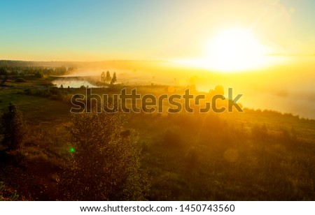 Sunrise on the river with fog. A river whirlpool for the dawn. Trees in fog on the river bank in morning. The rays of dawn sunlight illuminate the clearing with wildflowers and grass. #1450743560