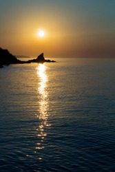 sunrise on the sea, ocean, against the backdrop of a cliff, glare from the sun in the water in the same vertical line with a cliff, photo in warm and cold colors
