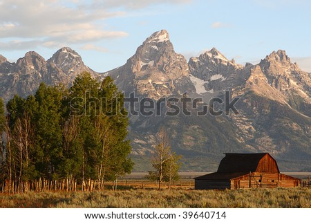 Sunrise on the Tetons Mountain range with a beautiful and historic Mormon barn