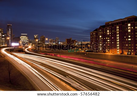 Sunrise or sunset downtown Atlanta skyline showing trails of car headlights and tail lights