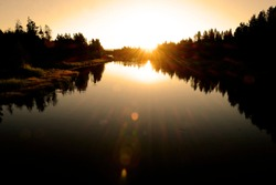 Sunrise or Sunset on River with Forest of Pine Trees beams of light