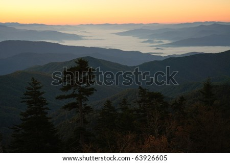 sunrise over a foggy valley and mountain ranges