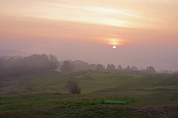 Sunrise over a misty Cotswolds landscape looking from the summit of Painswick Beacon, over the golf links towards Cranham, The Cotswolds, Gloucestershire, UK