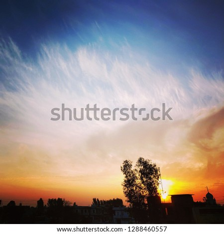 sunrise over a town with clouds and blue sky in the background. #1288460557
