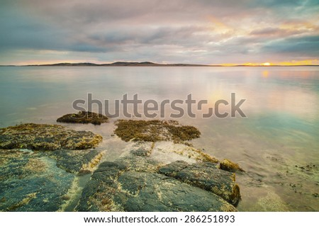 Sunrise over a very calm ocean with flat rocks in the foreground.