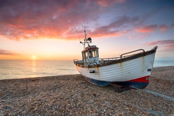 Sunrise over an old fishing boat on the beach at Dungeness on the Kent coast