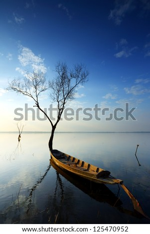 Sunrise over dam with dead trees and fishing boat at Thailand