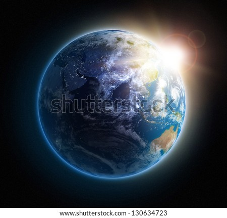 Sunrise over Earth seen from space with lights glowing in urban areas.