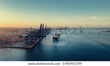 Sunrise over Felixstowe Container Port as two tugs shepherd a container ship from under blue gantry cranes with rows of brightly coloured shipping containers stacked behind them  ストックフォト ©