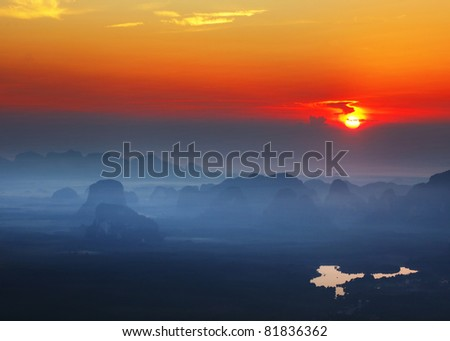 Sunrise over foggy valley with limestone mountains
