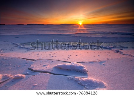 Sunrise over frozen and snowy coastline of Finland