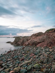 Sunrise over Guernsey beach and rocks