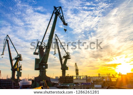 Sunrise over historical port cranes in the industrial part of the city Gdansk (Gdańsk) in Poland (Polska). Popular tourist destination - shipyard known all over the world. stock photo