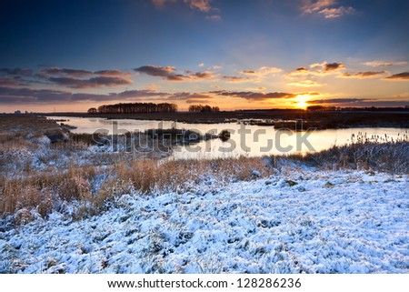 sunrise over lake in snowy winter #128286236
