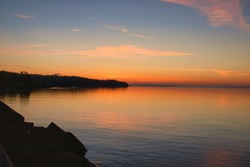 Sunrise over Lake Superior with an orange and blue sky and rocks in the foreground.