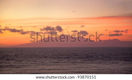 Sunrise over Lombok Island, Indonesia, with the Lombok Strait in the foreground.