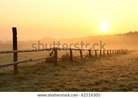 Sunrise over misty grassland with wooden fence in the foreground. Photo taken in October.