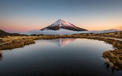 Sunrise over Mount Taranaki volcano with reflection in lake. Taranaki volcano with snow sorrounded by morning fog mirroring in water. Mirror pools at the Pouakai hut track in North island, New Zealand