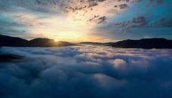 Sunrise over mountain hils covered with gray mist. Aerial panoramic drone shot