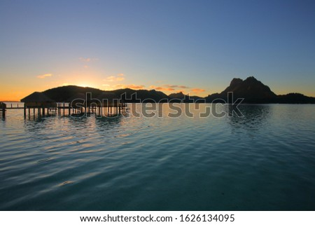 Sunrise over mountains and over water huts in Bora Bora