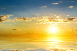 sunrise over ocean. tranquil summer seascape.the bright summer sun rising from the ocean waters and reflecting in the waves.
