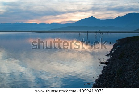 Sunrise over partially submerged dead tree branches in Lake Isabella in the southern Sierra Nevada mountains in central California United States #1059412073