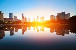 Sunrise over pond in a city. Kuala Lumpur skyline