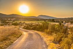 Sunrise over road in highland limestone karst plateau landscape on Causse de Blandas, Occitanie, France