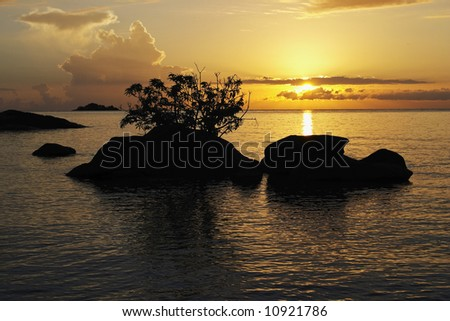 Sunrise over sihouetted rocks, Makuzi Beach, Malawi. The rising sun is reflected in the tranquil rippled waters of Lake Malawi. Salmon pink and orange clouds fill the sky.