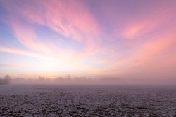 Sunrise over snow covered meadow with ground fog in winter