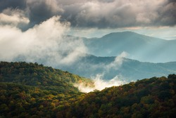 Sunrise over the autumn morning fog on the Blue Ridge Parkway in the Appalachian Mountains of western NC. Clouds envelope the mountain layers with sunshine lighting up the fall foliage in the valley.