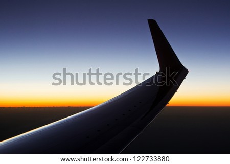 Sunrise over the clouds with the silhouette of the wing of a plane - stock photo