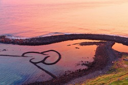 Sunrise over the Double-Heart Stacked Stones or Twin-Heart Fish Trap, which is a fishing weir and a popular tourist attraction in Cimei, Penghu, Taiwan, with golden sunlight reflected in the seawater